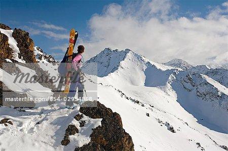 Woman Telemark Skier stands on ridge viewing Mount Tikishla Chugach Mountains & State Park Alaska Winter