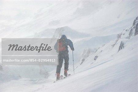 Dans l'arrière-pays skieur skis à travers les montagnes Chugach près de Girdwood Alaska avec soufflage de la neige et la faible visibilité
