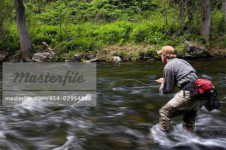 Flyfisherman fishing for  trout on upper end of Russian River Kenai Peninsula Alaska Summer