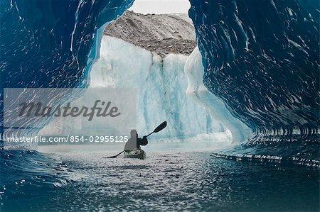Sea Kayaker paddles through an ice cave amongst giant icebergs near Bear Glacier in Resurrection Bay near Seward, Alaska