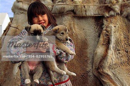 Alaskan Inupiat Eskimo girl w/puppies Kotzebue W Alaska