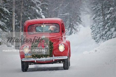 Homme conduisant un pick-up Ford de vintage 1941 avec une guirlande de Noël sur le front pendant l'hiver dans le centre-sud, Alaska