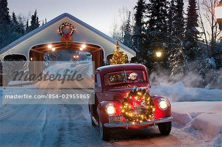 Homme conduisant un pick-up Ford de vintage 1941 grâce à un pont couvert avec une guirlande de Noël sur le grill et un arbre dans le dos pendant l'hiver dans le centre-sud, Alaska