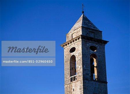 Le clocher de l'église de Santo Stefano di Sessanio avec la lune derrière au crépuscule, Abruzzo, Italie.