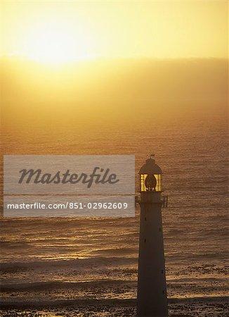 Vagues à venir à terre devant le phare de Kommitjie au crépuscule, péninsule du Cap, Afrique du Sud.