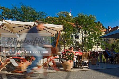 Cyclists passing the riverside cafes,Ljubljana Slovenia