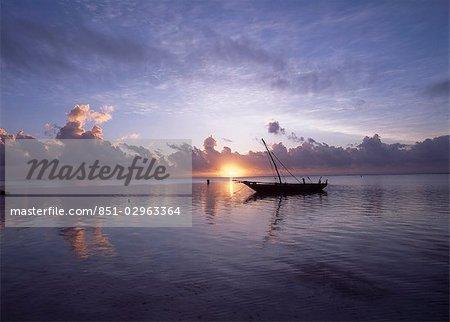 Dhow in calm waters at low tide at dawn,Matemwe beach,Zanzibar,Tanzania.