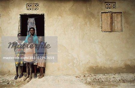 Famille debout devant leur maison, de l'Ouganda.
