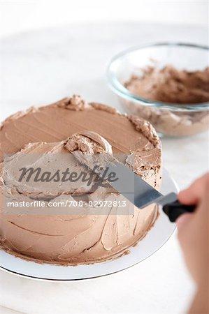 Person, die Vereisung ein Schokoladenkuchen