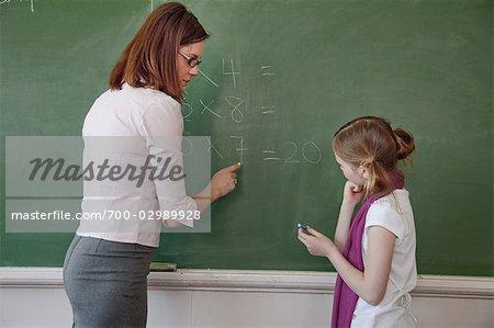 Lehrer und Schüler, die Mathematik auf der Tafel zu tun