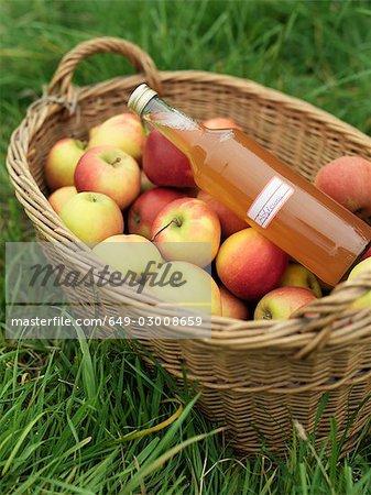 Pommes dans le panier avec une bouteille de jus