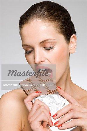 Female beauty model eating chocolate