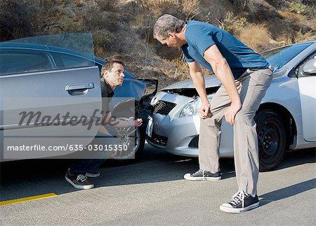 Zwei Männer Auto Kollision Schäden untersuchen