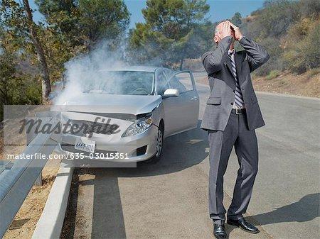 Frustriert Geschäftsmann stand neben Auto zerstört auf Geländer