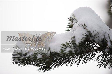 Papillon décoratif doré sur branche couverte de neige