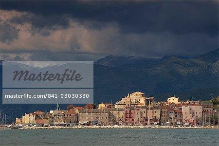 Nuages sombres sur les collines et les toits de la ville de St-Florent, le Cap Corse, la Corse, France, Méditerranée, Europe