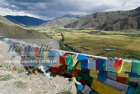 Drapeaux de prière et une vue sur les champs cultivés, château de la Yumbulagung, Tibet, Chine, Asie
