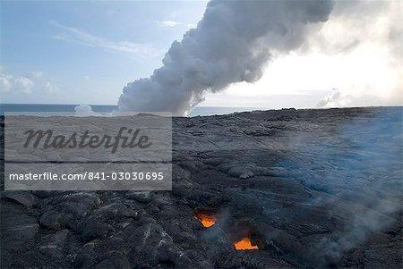 """Puits de lumière, par l'intermédiaire de lave refroidie à la lave en fusion ci-dessous, avec des panaches de vapeur comme la lave atteint la mer au-delà du volcan Kilauea, Hawaii Volcanoes National Park, patrimoine mondial de l'UNESCO, l'île d'Hawaii (Big Island """""""", Hawaii, États-Unis d'Amérique, l'Amérique du Nord"""