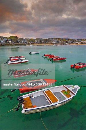 Formation des étranges nuages dans un ciel orageux au coucher du soleil, avec petites vedettes rouges à louer avec une marée montante dans le havre de St. Ives, Cornwall, Angleterre, Royaume-Uni, Europe