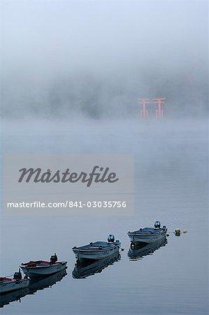 Small boats in the mist on lake Ashi (Ashiko),Hakone,Kanagawa prefecture,Japan,Asia