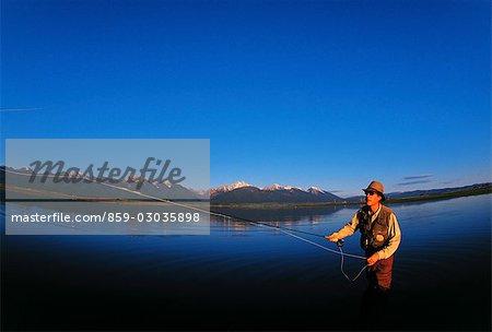 L'homme pêche à la mouche dans le lac