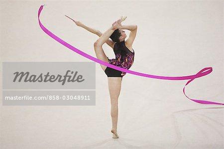 Une jeune fille jouant de gymnastique rythmique avec jambe soulevée