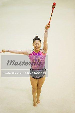 Woman performing rhythmic gymnastics with clubs