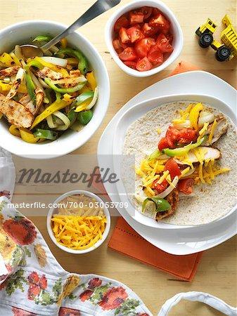 Hähnchen-Fajitas mit gegrilltem grünen und gelben Paprika, Zwiebeln, Tomaten und Cheddar-Käse