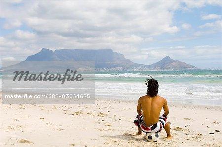 Jeune garçon assis sur le ballon de football sur la plage en regardant la montagne de la Table, vue de la Table, Cape Town, Province occidentale du Cap, en Afrique du Sud
