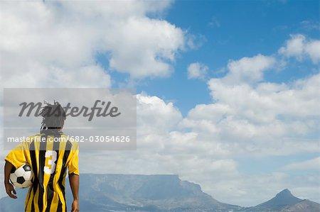 Joueur de soccer, tenir le ballon sous le bras en regardant la montagne de la Table, vue de la Table, Cape Town, Province occidentale du Cap, en Afrique du Sud
