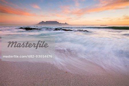 Surfer sur la plage de la baie de la Table, avec la montagne de la Table en arrière-plan au coucher du soleil, Bloubergstrand, Province du Western Cape, Afrique du Sud