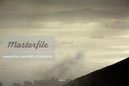 Trois navires dans la baie brumeuse de la Table avec la silhouette des immeubles de la ville en premier plan, tête de Lion, Cape Town, Province occidentale du Cap, en Afrique du Sud