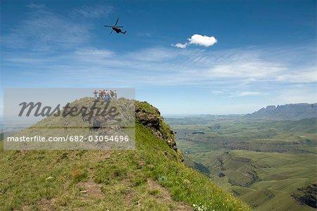 Oryx en hélicoptère les randonneurs de passage rocheuses affleurent, avec pointe de Tanger et peu Berg à distance, cathédrale haute gamme, Ukahlamba parc de Drakensberg, KwaZulu-Natal, Afrique du Sud