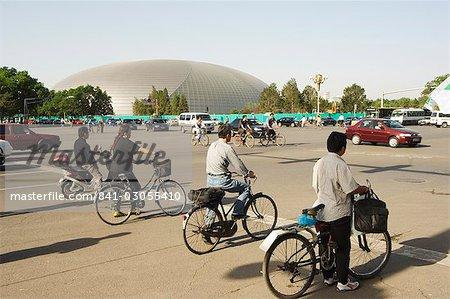 Le Théâtre National, conçu par l'architecte français Paul Andreu et les cyclistes au transport en Asie centrale de Pékin, Beijing, Chine,