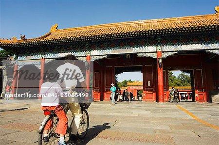 Un cycliste à une porte de Zijin Cheng The Forbidden City Palace Museum, patrimoine mondial UNESCO, Beijing, Chine, Asie