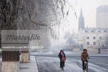 Cyclistes dans un paysage hivernal et l'église catholique dans la ville de Jilin, Jilin Province, Chine, Chine, Asie