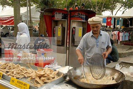 Fournisseur de produits alimentaires y fait frire des aliments à l'extérieur du marché Central, Kuala Lumpur, en Malaisie, l'Asie du sud-est, Asie
