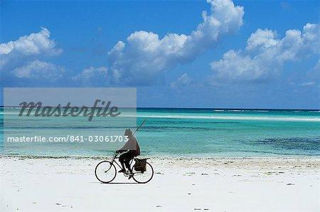 A man riding his bicycle of Kiwengwa beach, island of Zanzibar, Tanzania, East Africa, Africa