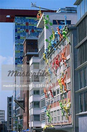 Flossies figures covering a building facade at the Medienhafen (Media Harbour), Dusseldorf, North Rhine Westphalia, Germany, Europe