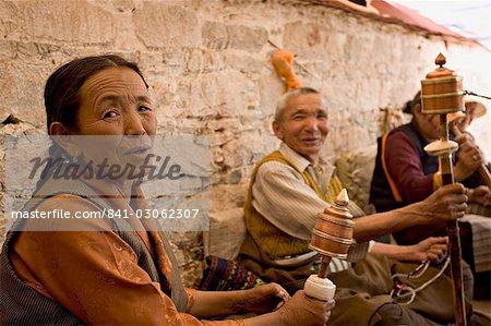 Tourner les moulins à prières sous un dais de garder le soleil, sur un toit du monastère dans le Bharkor, Lhassa, Tibet, Chine Asie