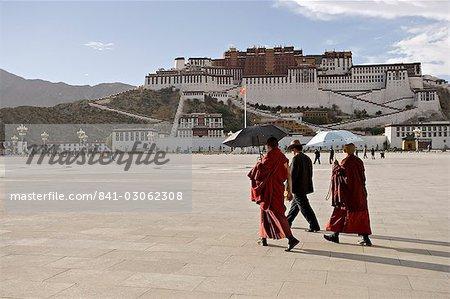 Moines transportant des parapluies pour protéger contre le soleil, en face du Palais du Potala, patrimoine mondial UNESCO, Lhassa, Tibet, Chine, Asie