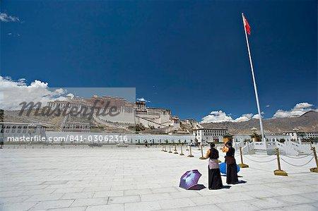 Deux femmes tibétaines, prière, devant le palais du Potala, patrimoine mondial UNESCO, avec le chinois drapeau vers la droite, Lhassa, Tibet, Chine, Asie