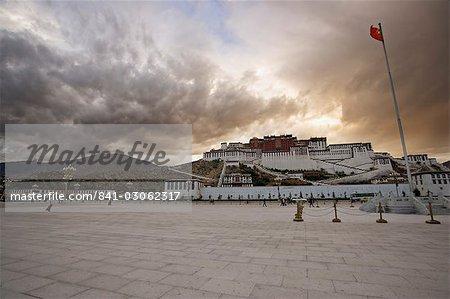 Le drapeau rouge de la Chine vole sur place Potala sur un après-midi orageux devant le palais du Potala, patrimoine mondial UNESCO, Lhassa, Tibet, Chine, Asie