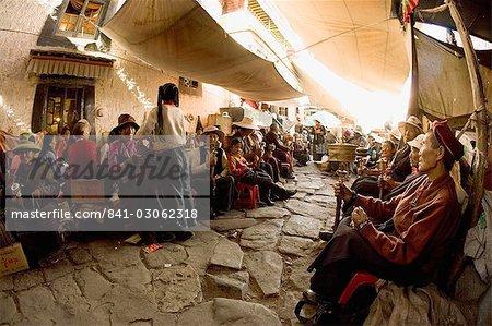 Pèlerins tournent les moulins à prières en dehors d'un monastère dans le Bharkor, Lhassa, Tibet, Chine, Asie