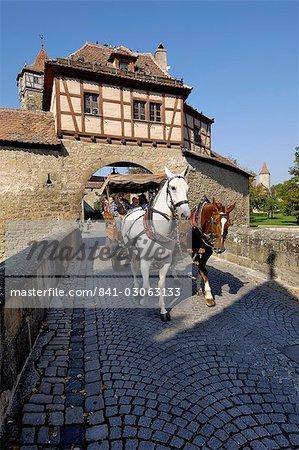 Cheval tourisme et transport en passant par la Rodertor (porte de Roder), porte dans les murs de la ville, Rothenburg ob der Tauber, Bavière (Bayern), Allemagne, Europe