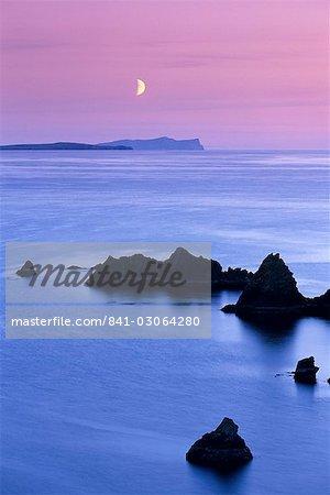 Coucher de soleil sur le sable Wick et lune montante sur Foula en distance, Eshaness, Shetland, Ecosse, Royaume-Uni, Europe