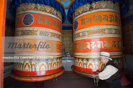 Vieille femme poussant les moulins à prières, Si Jingang, Kangding, Sichuan, Chine, Asie