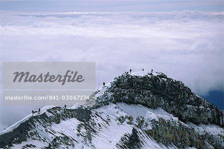 Randonneurs dans le dôme crête près du sommet de 2797 Mont Ruapehu, plus forte et plus actif des volcans en Parc National, Parc National de Tongariro, patrimoine mondial de l'UNESCO, plateau central, North Island, Nouvelle-Zélande, Pacifique
