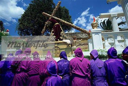 Hommes en robes pourpres transportant d'énorme flottant sur l'un de l'Amérique centrale le célèbre Pâques processions, Antigua, Guatemala,