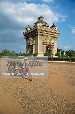 Femme sur un vélo avec une remorque roule devant le monument de Anousavari à Vientiane, au Laos, Indochine, Asie du sud-est, Asie